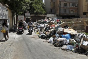 epa04857539 Lebanese citizens cover their faces as they walk past piles of garbage left on a street in Beirut, Lebanon, 23 July 2015. According to local reports due to a growing dispute over garbage collection with the main company responsible for the service Sukleen, although streets are being swept garbage remians uncollected on Beirut's streets.  EPA/NABIL MOUNZER