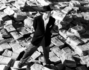 CITIZEN KANE, Orson Welles, 1941, astride stacks of newspaper